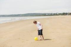 Årig pojke som tio spelar fotboll på stranden Royaltyfria Bilder