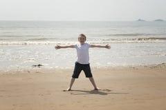 Årig pojke som tio spelar på stranden Arkivbild
