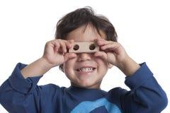 Årig pojke som två ser till och med hålen av ett kvarter Fotografering för Bildbyråer