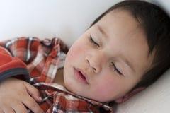 Årig pojke som två sover på en soffa Royaltyfria Foton