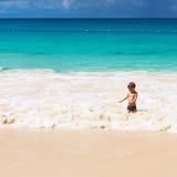 Årig pojke som två spelar på stranden Arkivfoto