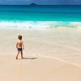 Årig pojke som två spelar på stranden Arkivbild
