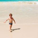 Årig pojke som två spelar på stranden Royaltyfria Foton