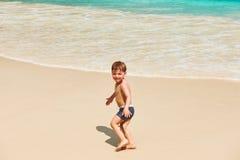 Årig pojke som två spelar på stranden Fotografering för Bildbyråer