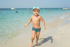 Åriga fyra behandla som ett barn pojken som spelar på stranden på Seychellerna Royaltyfria Bilder