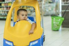 Åriga gulliga ledsna lite 2 behandla som ett barn pojkebarnet i den lilla leksak-bilen spårvagnen på supermarket, farsa eller upp arkivbild