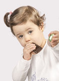 Åriga gulliga två behandla som ett barn äta choklad Arkivbilder