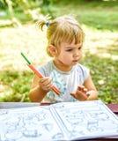 Åriga härliga två behandla som ett barn flickateckningen i en färgläggningbok Royaltyfri Fotografi