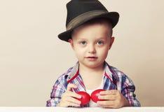 4 åriga lilla och gulliga pojke i en hatt och skjortainnehavhänder fotografering för bildbyråer