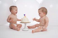Åriga tvilling- pojkar en med födelsedagkakan Arkivfoton