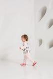 Årigt barn som står den near vita väggen i studio royaltyfria foton