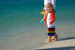 Årigt litet barn som två går på stranden med modern Fotografering för Bildbyråer