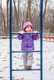 Årigt parkerar spela för liten flicka en utanför i vinter lekplatsen Royaltyfri Bild