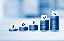 Årligt bonusbegrepp - ord av bonusen på buntmynttrappuppgången för uppmuntranmoral på tabellkontorsföretaget royaltyfri fotografi