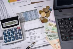 Årsbudget, marknadsföringsforskning och affärsrapport med bärbara datorn, euroräkningar, mynt royaltyfri fotografi