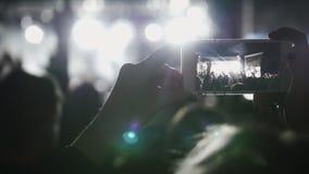 Åskådare på videoen för musikkonsertskytte på smartphonen royaltyfri foto