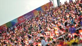 Åskådare som vinkar Singapore flaggor under nationell dag, ståtar repetitionen (NDP) 2013 Arkivfoton