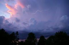 Åskväder med lightening under solnedgång Arkivfoto