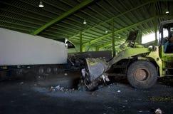 Återanvänd överblicken av renhållningen med den gröna bulldozeren Arkivfoto