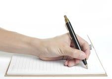 Återanvänd anteckningsboken med den hållande pennan för den härliga handen för att skriva Arkivfoto