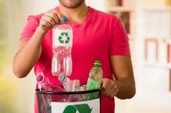Återanvänd och kassaskåpet, le den unga mannen som mycket sätter en plast- flaska inom av en liten svart avskrädesamlare av plast Arkivbilder