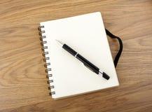 Återanvänd pappers- anteckningsbok med den svarta elastiska musikbandet och pennan Arkivbild