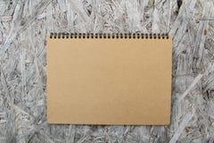 Återanvänd pappers- anteckningsbok på trä Arkivbild