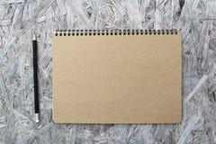 Återanvänd pappers- anteckningsbok på trä Fotografering för Bildbyråer