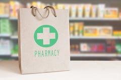 Återanvänd pappers- påse med en grön apoteklogo i ett apotek tomt kopieringsutrymme Royaltyfri Foto