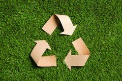 Återanvändning av symbolsnittet ut ur kraft papper på grönt gräs arkivfoto