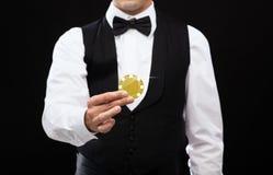 Återförsäljare som rymmer den guld- pokerchipen royaltyfri bild