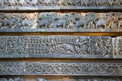 Återgivning av Arjuna-Kirata, Shiva som jagar svinet, på grunden av templet, Hoysaleshwara tempel, Halebidu, Karnataka royaltyfri fotografi