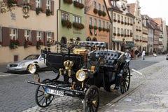 Återställd vagn som parkeras i kullerstenstreetscape arkivbild