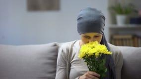 Återställning efter cancer, kvinna i sjalett som luktar blommor och tycker om liv stock video