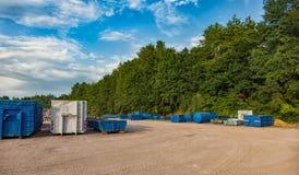 Återvinninggård med olika behållare Arkivbilder