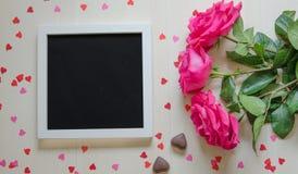 Åtlöje för dag för St-valentin` s tom upp med rosa rosor och fotoramen Arkivfoton