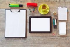 Åtlöje för kontorsskrivbord upp mall med minnestavlan, ilar telefonen, anteckningsboken och koppen kaffe Sikt från ovannämnt med