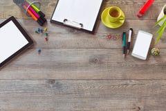 Åtlöje för kontorsskrivbord upp mall med minnestavlan, ilar telefonen och koppen kaffe Sikt från ovannämnt med kopieringsutrymme arkivfoton