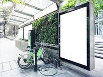 Åtlöje upp den ljusa asken för affischtavla på bussstationen med offentlig cykelparkering Arkivfoton