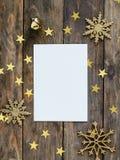 Åtlöje upp greetengkort på wood lantlig bakgrund med julpynt blänker snöflinga-, klocka- och guldstjärnakonfettier Invit Royaltyfri Foto