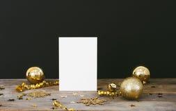 Åtlöje upp hälsningkort på wood lantlig mörk bakgrund med julpynt blänker snöflingor, struntsaker, klockan som, är slingrande och royaltyfria foton