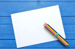 Åtlöje upp konstverk för teckning och text på en blå träbakgrund med fyra kulöra blyertspennor på hörnet av det tomma arket arkivfoton