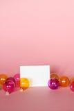 Åtlöje upp med inbjudankortet på ljus - rosa bakgrund med julprydnader Hälsningkort och colorfull genomskinliga glass Chri Royaltyfria Bilder