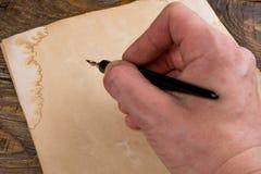 Åtlöje upp Räcka handstil med den gamla fjäderpennan på det gamla papperet Töm stället för en text kopiera avstånd Arkivbild
