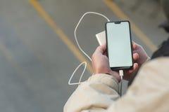 Åtlöje upp Smartphone med bärbar uppladdning i händerna av en man fotografering för bildbyråer