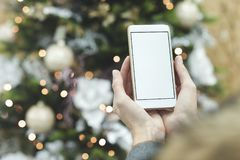 Åtlöje upp Smartphone med en selfiepinne i händerna av en man på bakgrunden av ställningarna Grabben tar en selfie på arkivbilder