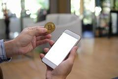 Åtlöje upp vit färg på skärmmobiltelefonen och guld- bitcoin i H Royaltyfri Fotografi