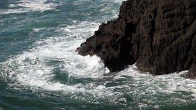 Åtsittande skott av vågor som svaller runt om Lava Headlands stock video
