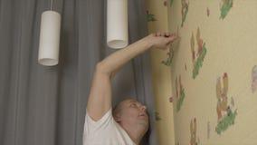 Åtsittande skruv för vuxen man i vägg vid den elektriska skruvmejseln DIY-begreppshemförbättring arkivfilmer