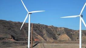 Åtsittande vindkraftturbiner stock video